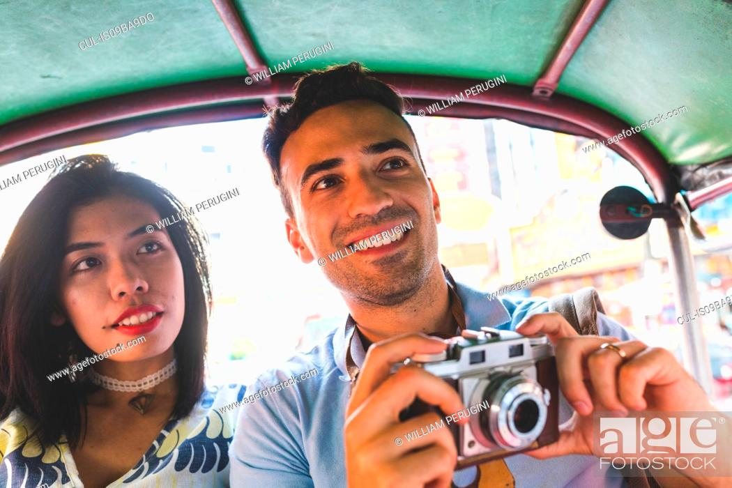 Stock Photo: Young tourist couple in auto rickshaw with camera, Bangkok, Thailand.