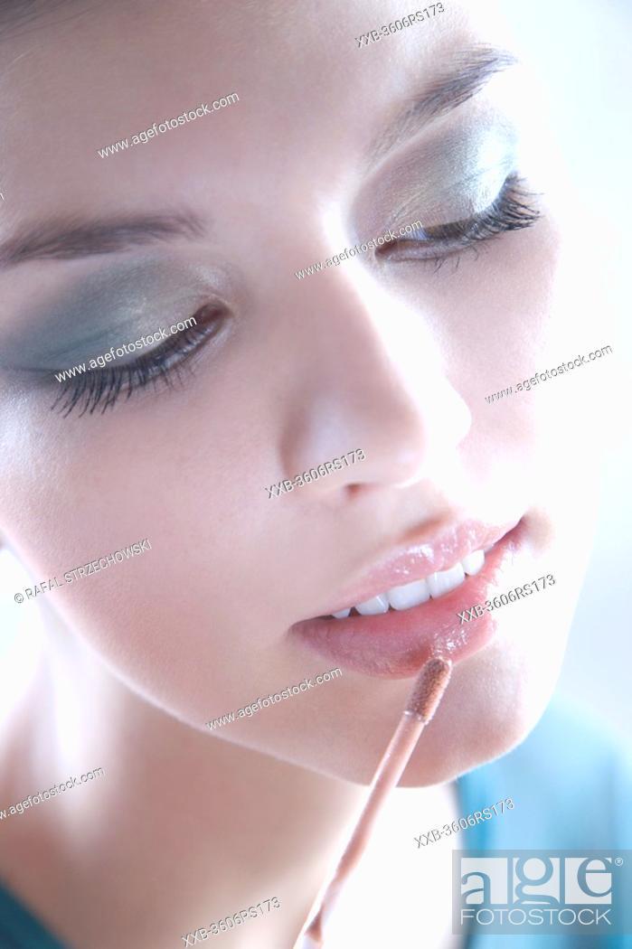 Stock Photo: woman using lipstick.