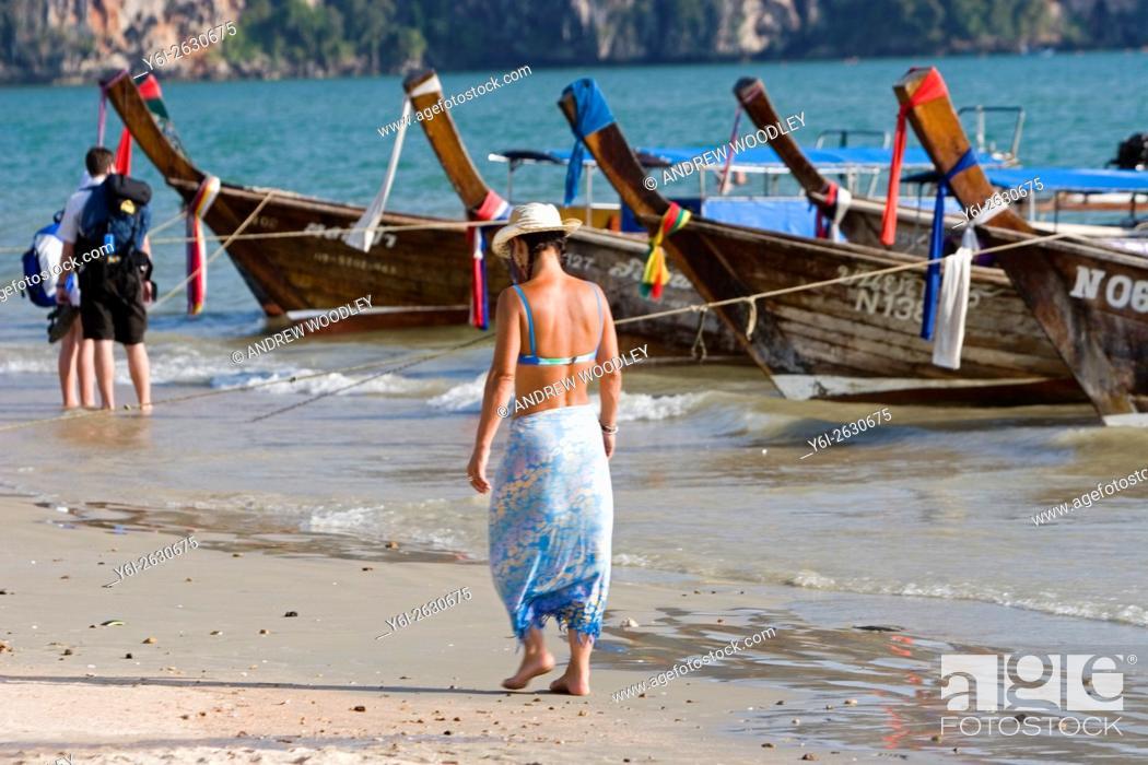 Imagen: Woman in sun hat bikini and sarong walks beach by longtail boats Ao Nang Thailand.