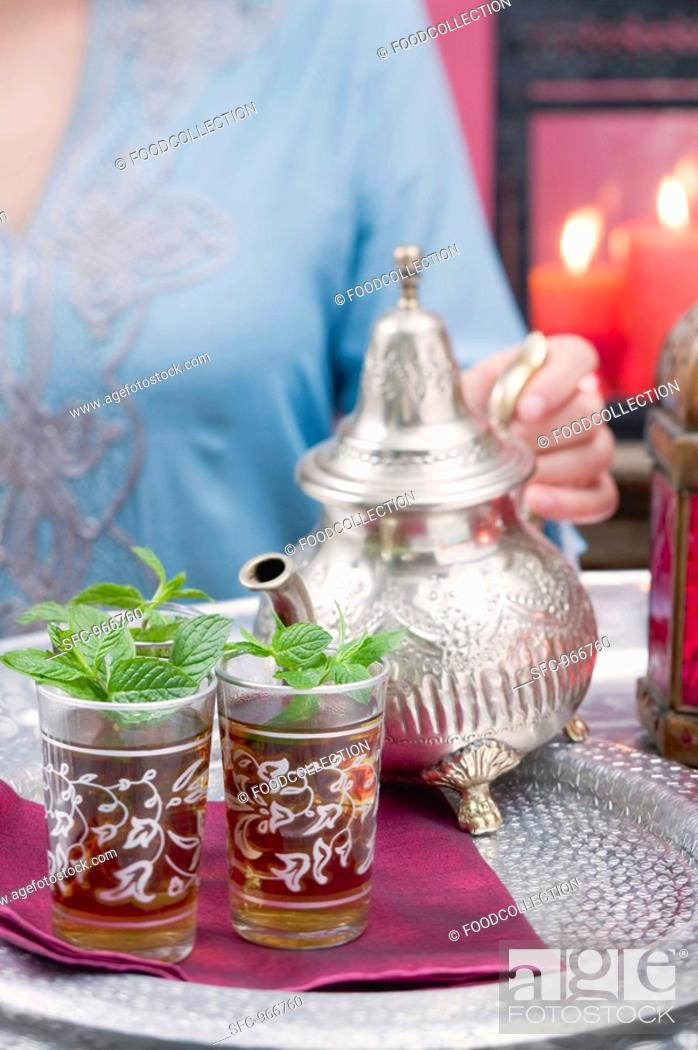Stock Photo: Woman pouring peppermint tea into glasses.