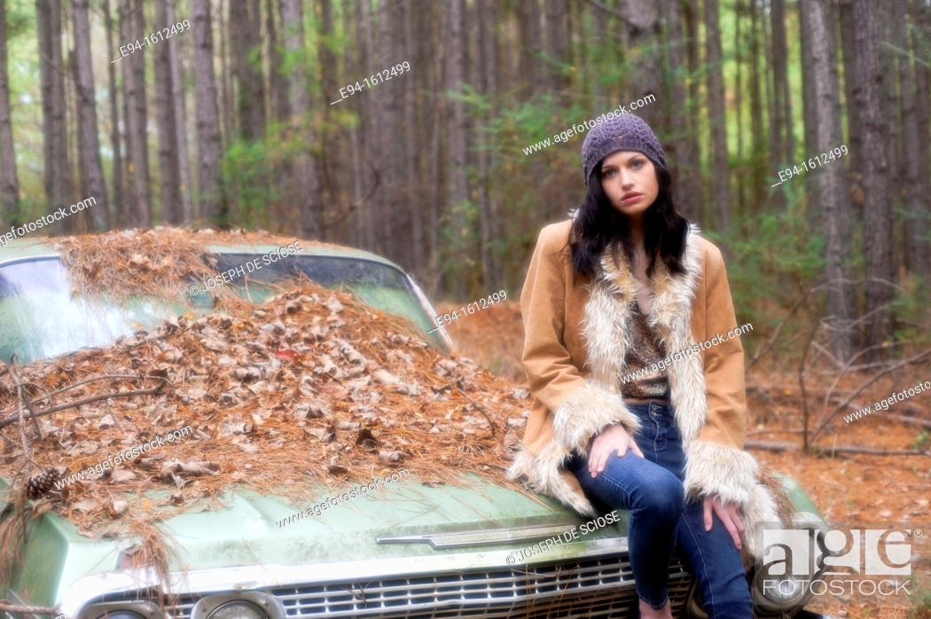 Stock Photo: Portrait of a 20 year old brunettte woman wearing a knit hat and a leather coat sitting on an old car in a forest setting.
