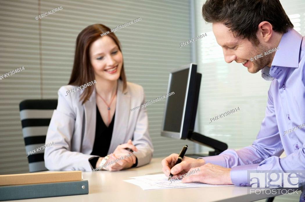 Stock Photo: Man signing documents with a female real estate agent sitting in front of him.
