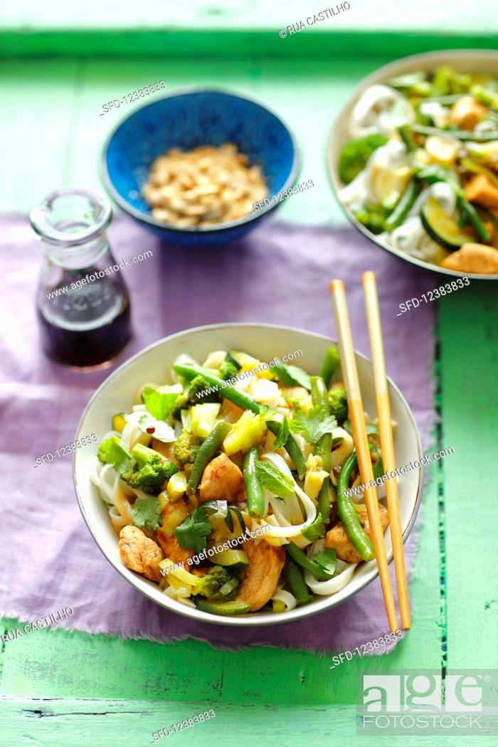 Stock Photo: Rice noodles with chicken, broccoli, green beans and herbs.
