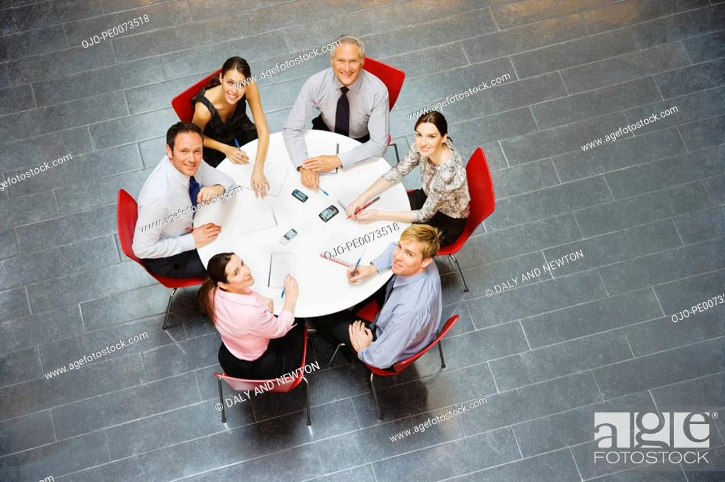 Stock Photo: Smiling business people sitting at round table and having a meeting.