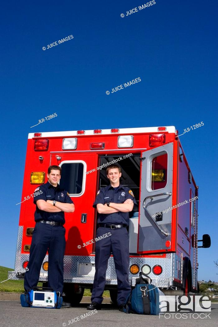 Stock Photo: Paramedic and colleague with arms crossed by open door of ambulance, portrait, low angle view.
