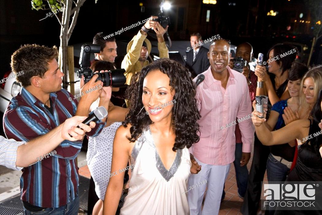 Stock Photo: Young woman surrounded in paparazzi, smiling.