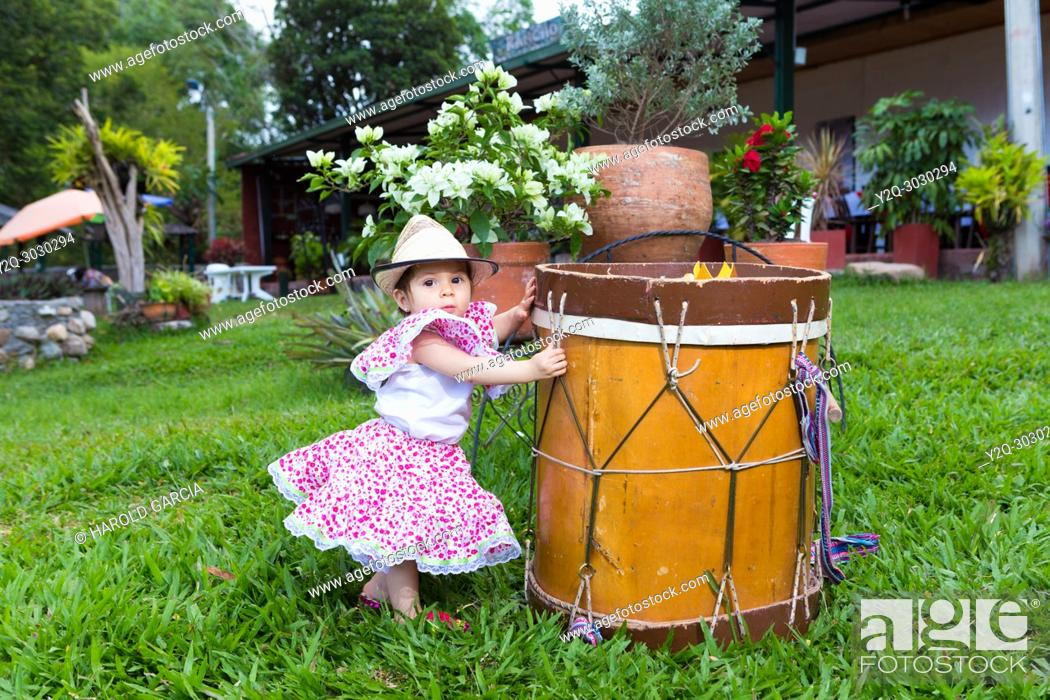Imagen: little girl in traditional dance dress with hat next to a drum.