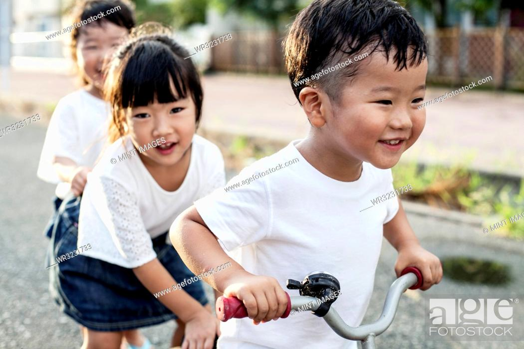 Stock Photo: Portrait of two Japanese girls and boy playing on street with a bicycle, smiling at camera.