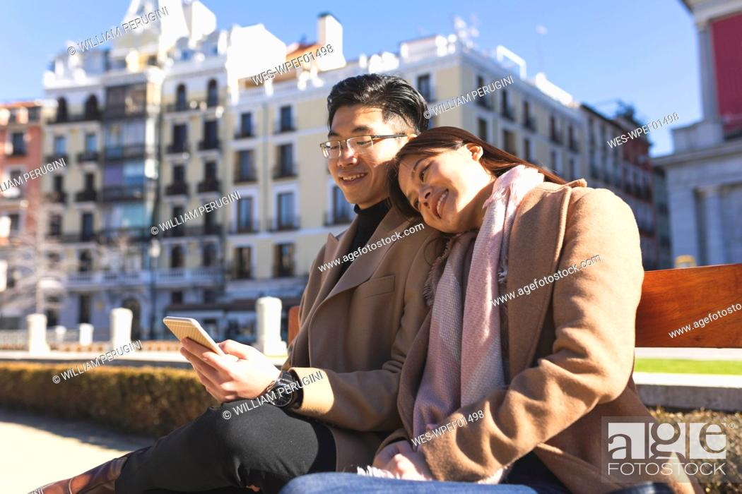 Photo de stock: Spain, Madrid, young couple resting on a bench and using cell phone in the city.