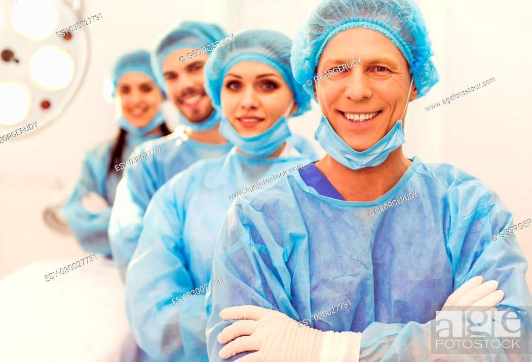 Stock Photo: Beautiful doctors are looking at camera and smiling, standing in line in a modern operating room.