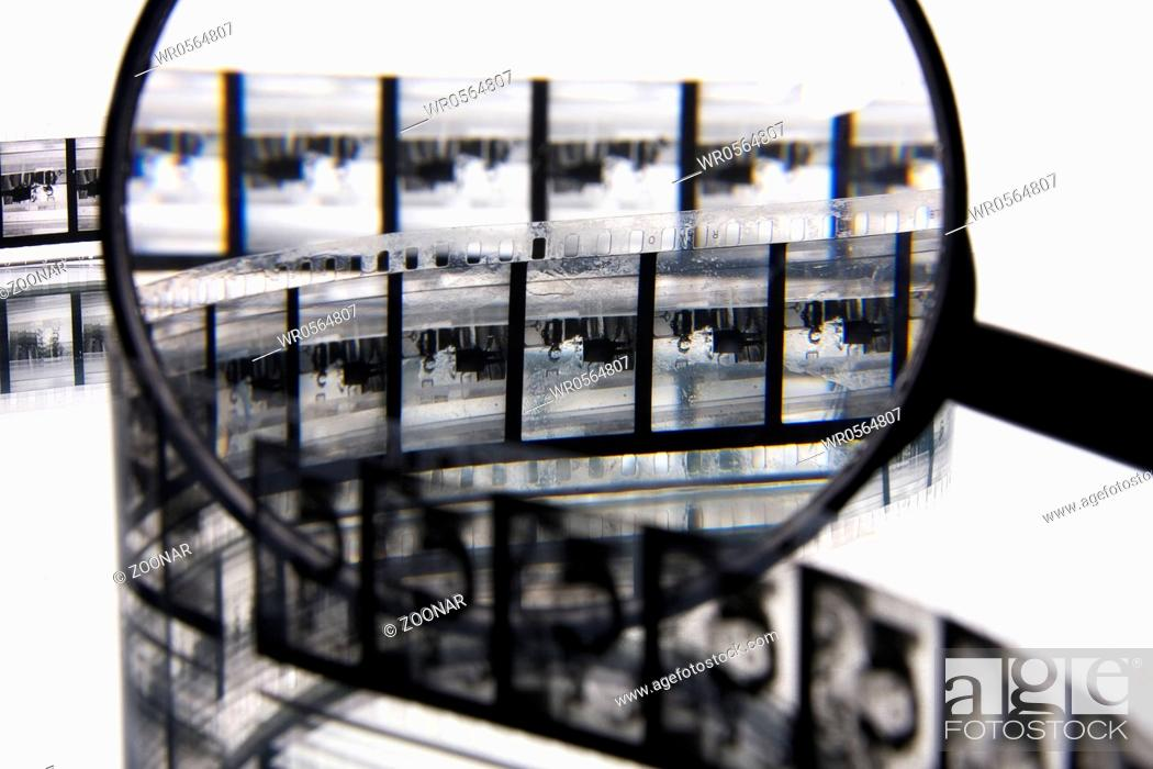 Stock Photo: Closer look to a black and white film strip with a magnifier.