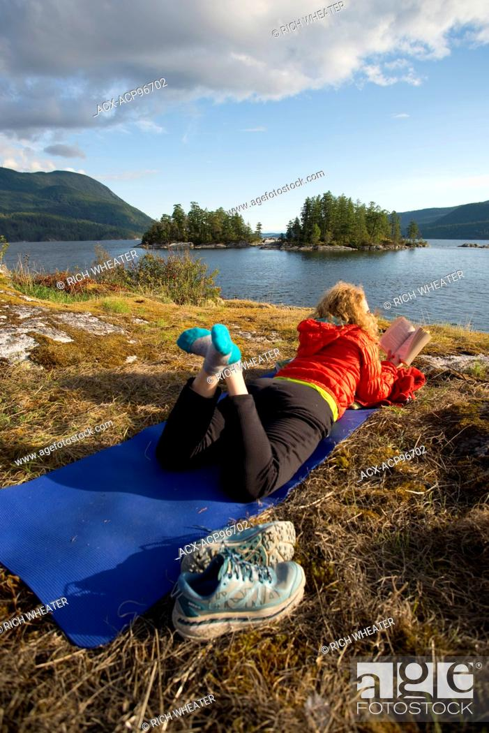 Stock Photo: Woman reading book on yoga mat while camping at Kunechin Point, Sechelt Inlet. Gibsons, Sunshine Coast, British Columbia, Canada.