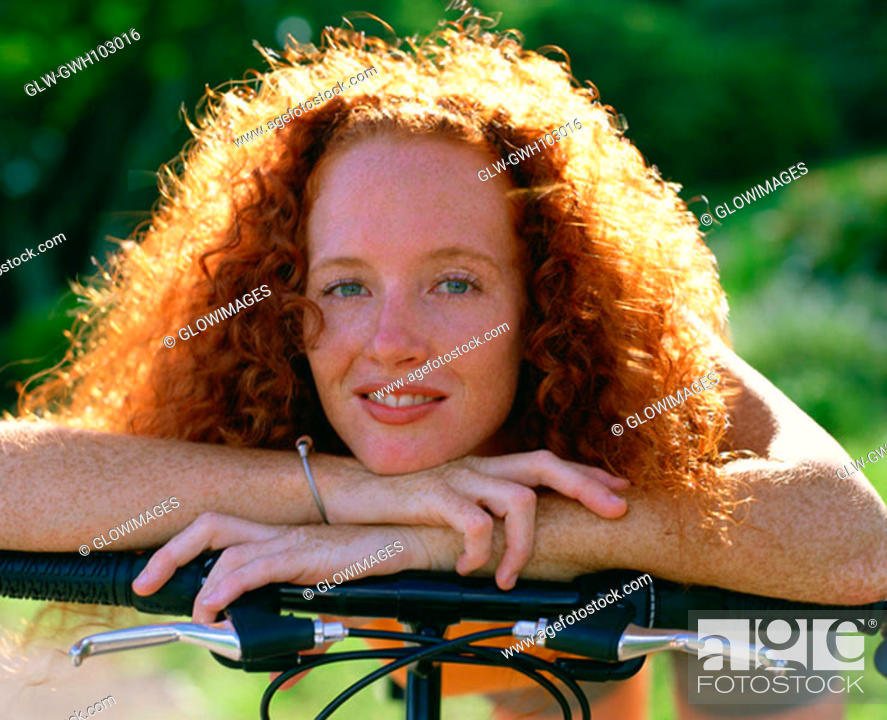 Stock Photo: Portrait of a young woman with a bicycle, Bermuda.