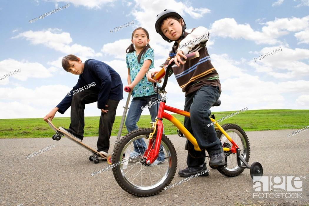 Stock Photo: Multi-ethnic children riding skateboard, scooter and bicycle.