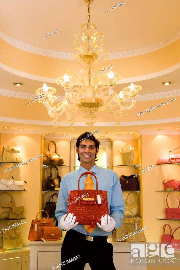 Stock Photo: Male shop assistant, in white gloves, standing in front of shelf display in glamorous boutique, holding red designer handbag, front view, portrait.