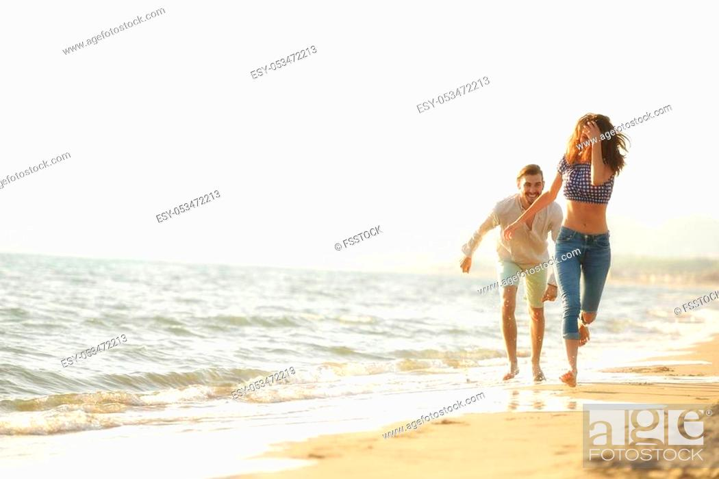 Stock Photo: happy couple waling on the beach and having fun.