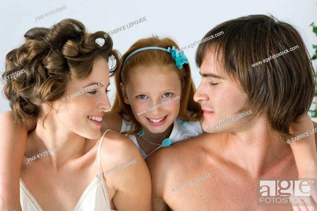 Stock Photo: Close-up of a couple smiling with their daughter.