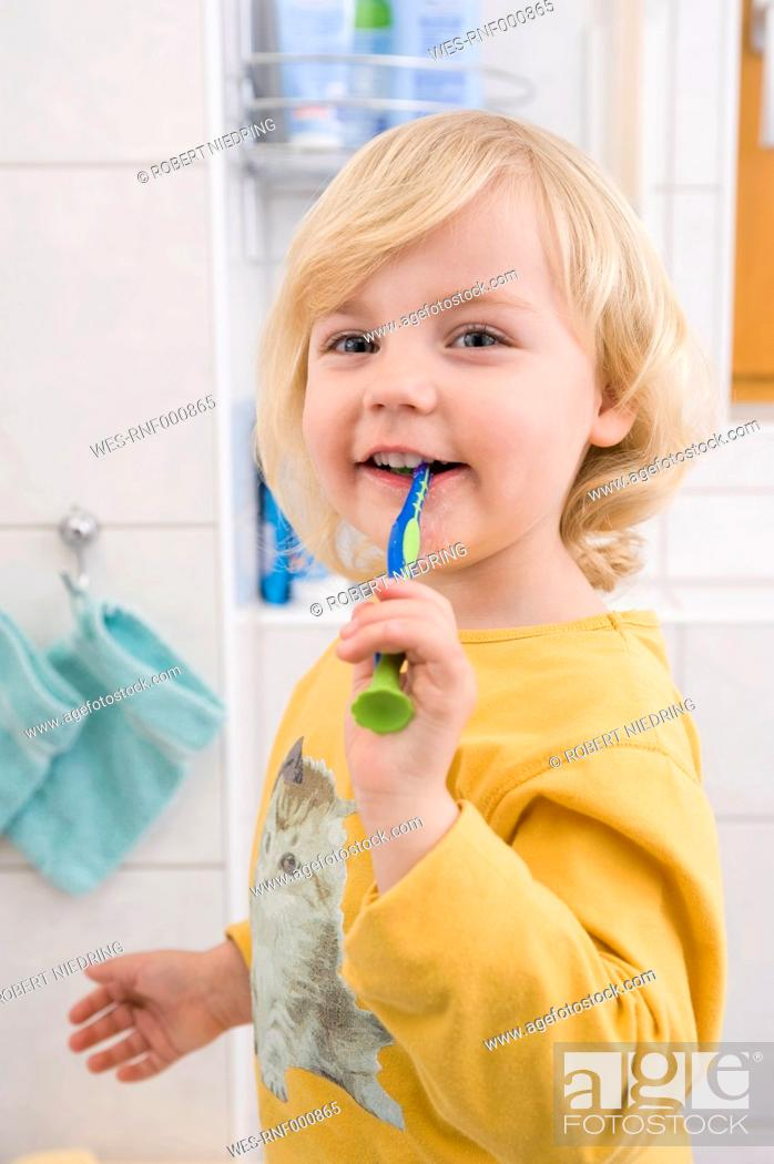 Stock Photo: Girl brushing her teeth in bathroom, close up.