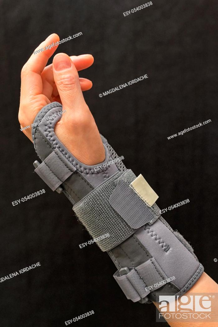 Stock Photo: Contused Woman Hand In Stabilizer on Black background.