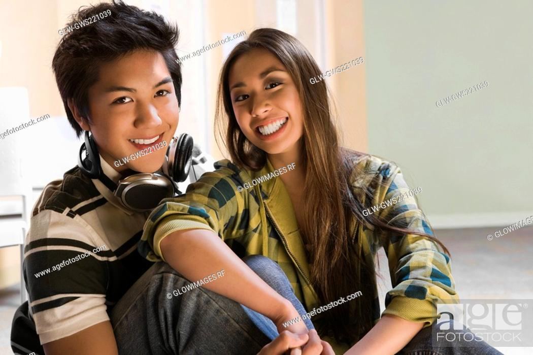 Stock Photo: Portrait of a young couple sitting together and smiling.