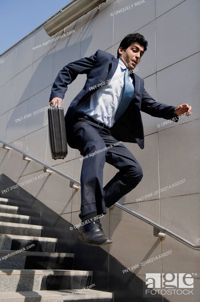 Stock Photo: Businessman rushing down stairs of a subway, Gurgaon, Haryana, India.