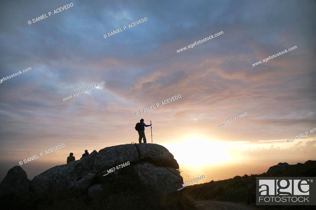 Stock Photo: Pilgrims arriving to Finisterre cape at sunset, Galicia, Spain, Europe.