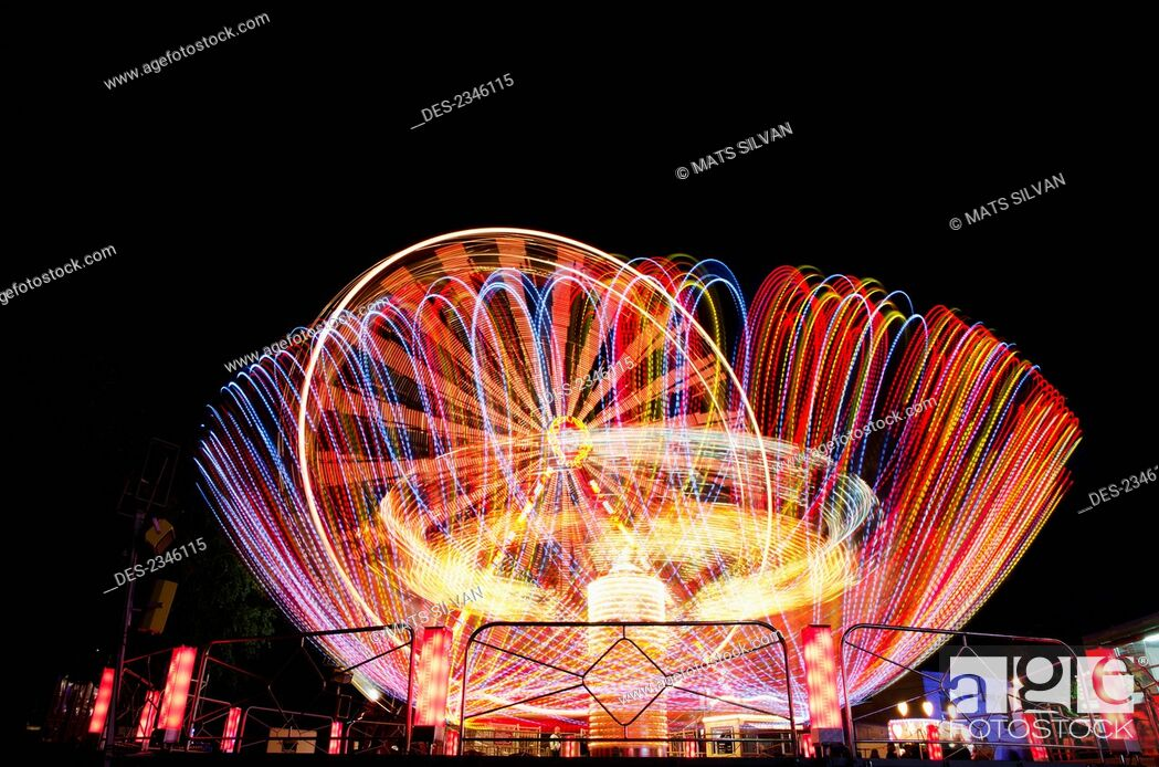 Stock Photo: Colourful lights blurring on amusement park rides at night; Locarno, Ticino, Switzerland.