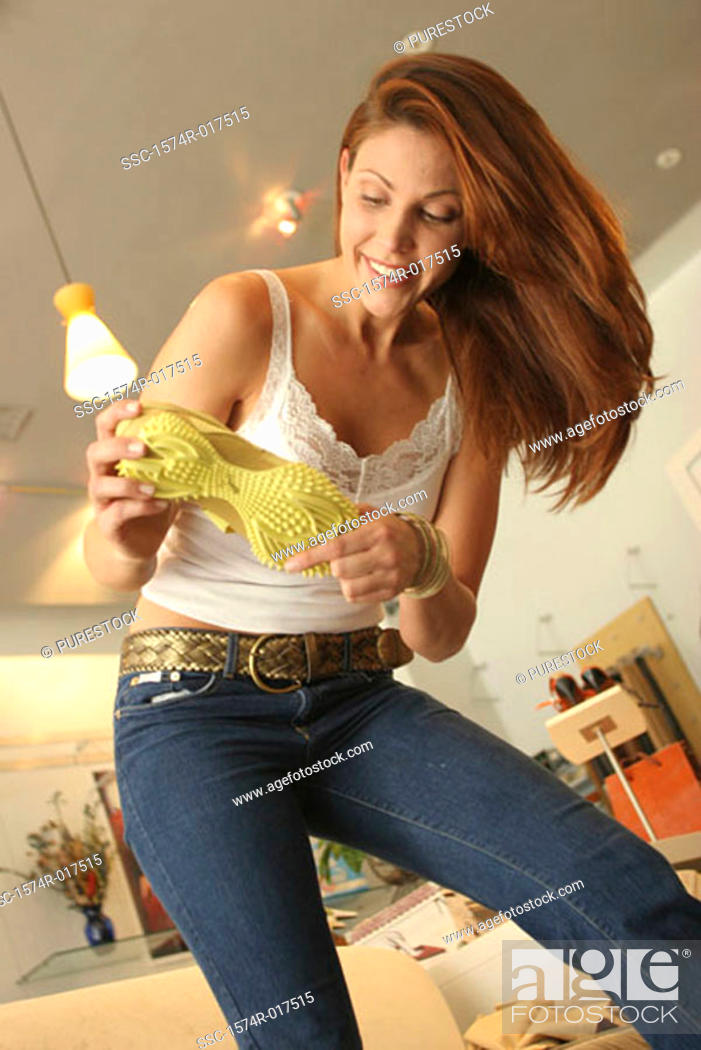 Stock Photo: Low angle view of a young woman holding a shoe in a shoe store.