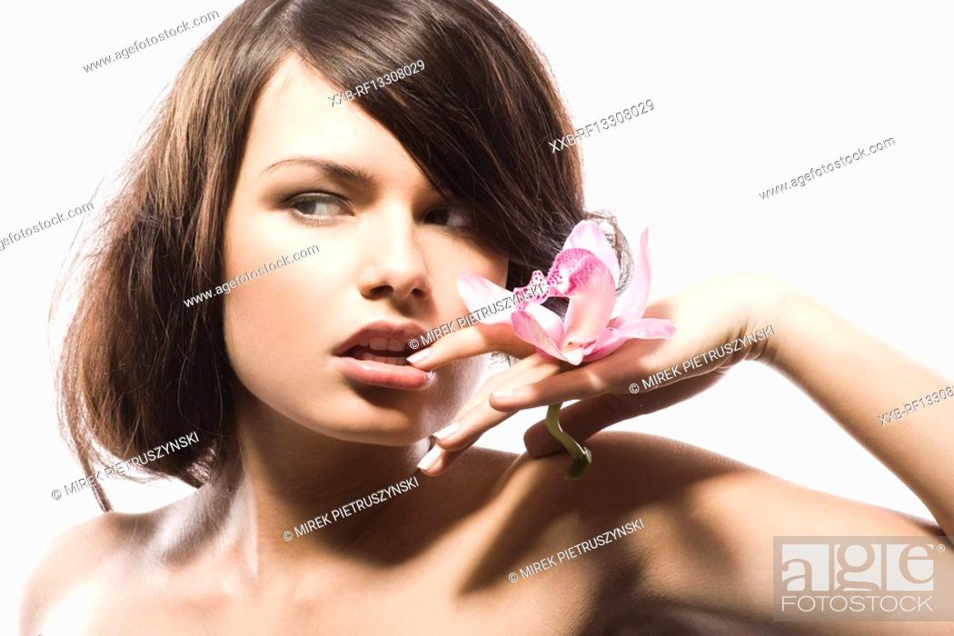 Stock Photo: young woman with pink orchid.