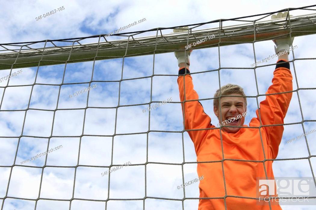 Stock Photo: Cheering goalkeeper hanging on goal.