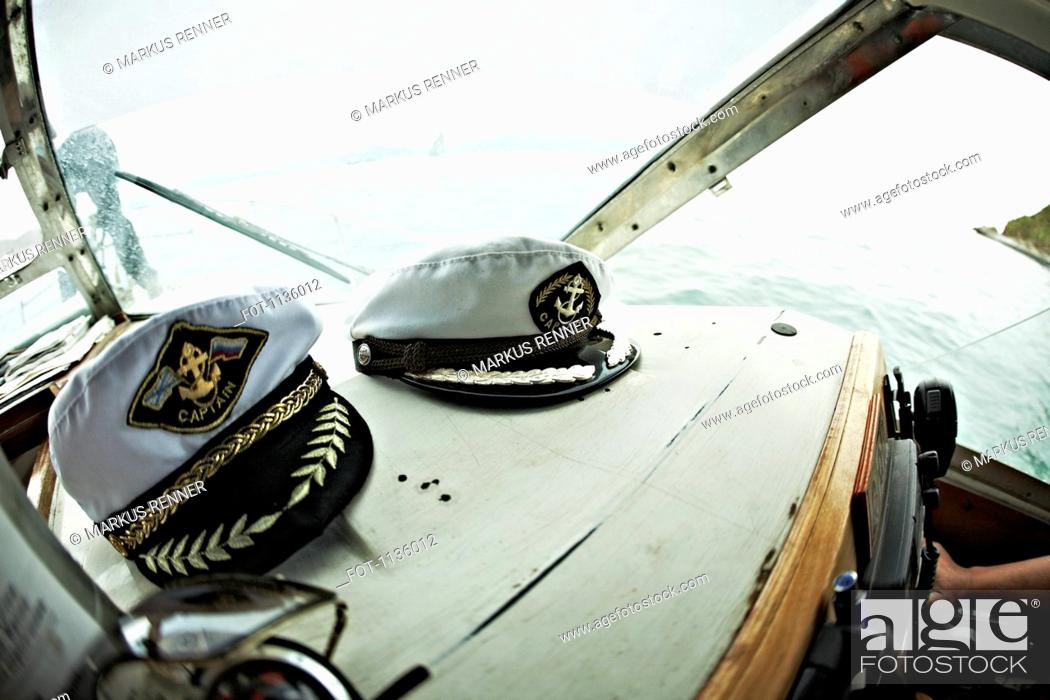Stock Photo: Two captain's hats resting on the dashboard of a motorboat, Avacha Bay, Russia.