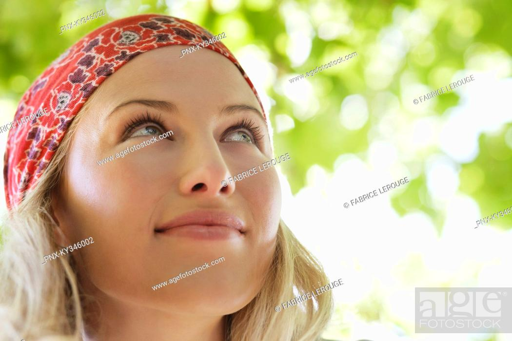Stock Photo: Close-up of a beautiful woman day dreaming.