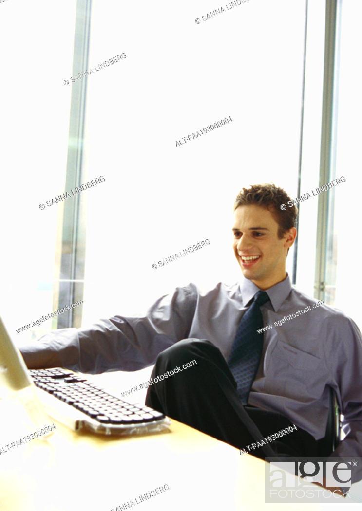 Stock Photo: Businessman sitting at desk smiling.