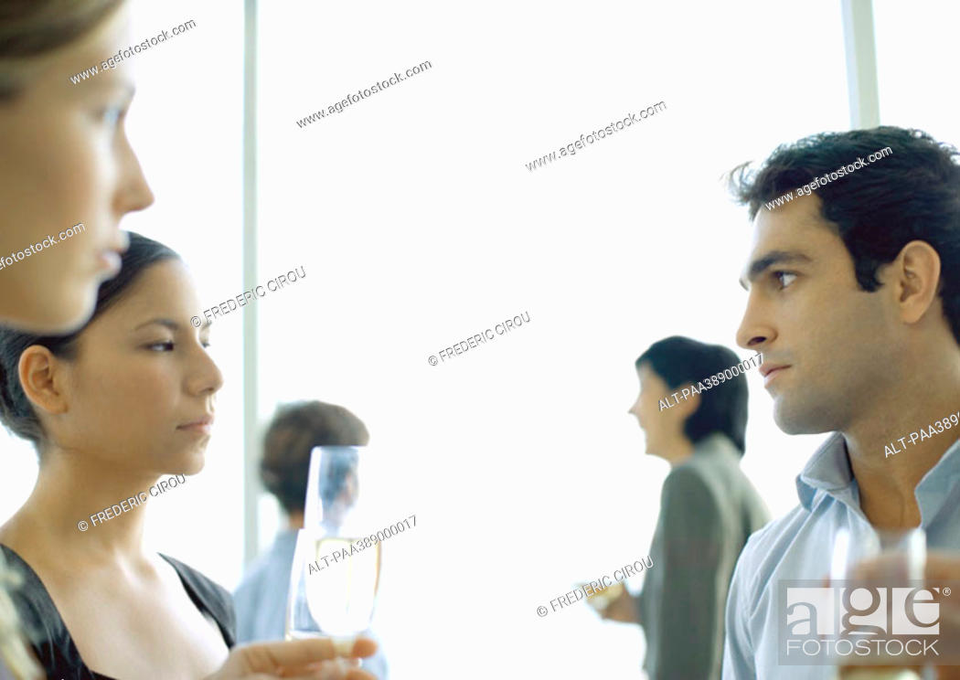 Stock Photo: Office party, man and woman glaring at each other.