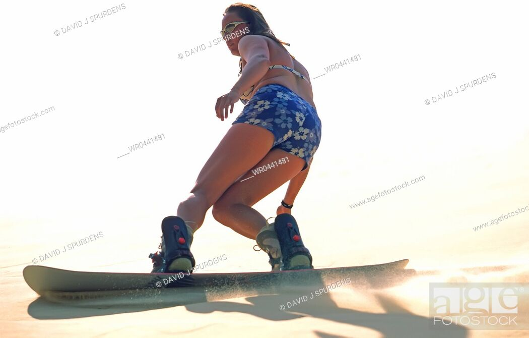 Stock Photo: Woman sandboarding on dunes.