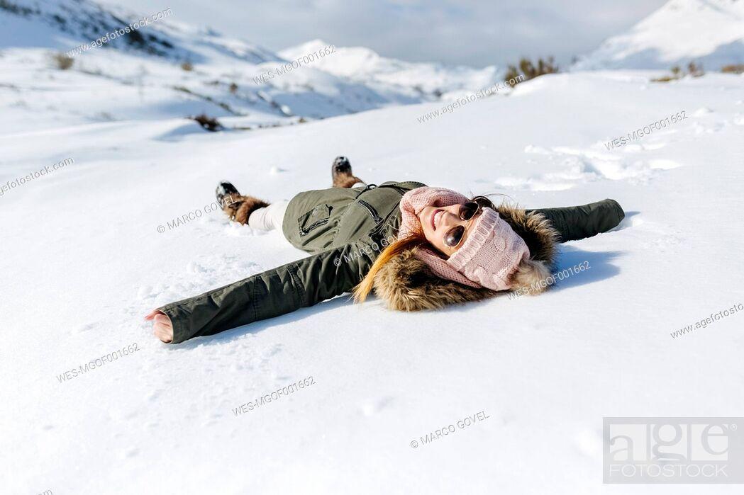 Stock Photo: Spain, Asturias, playful woman lying in snow.