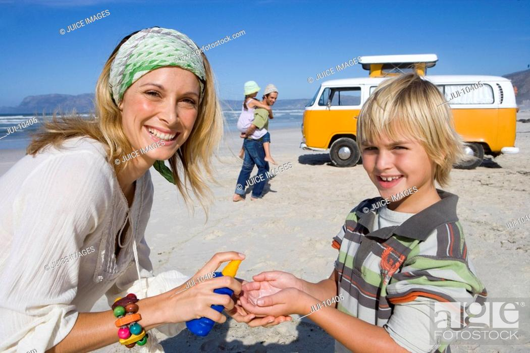 Stock Photo: Family of four on beach, mother applying sunscreen to son 6-8, smiling, portrait.