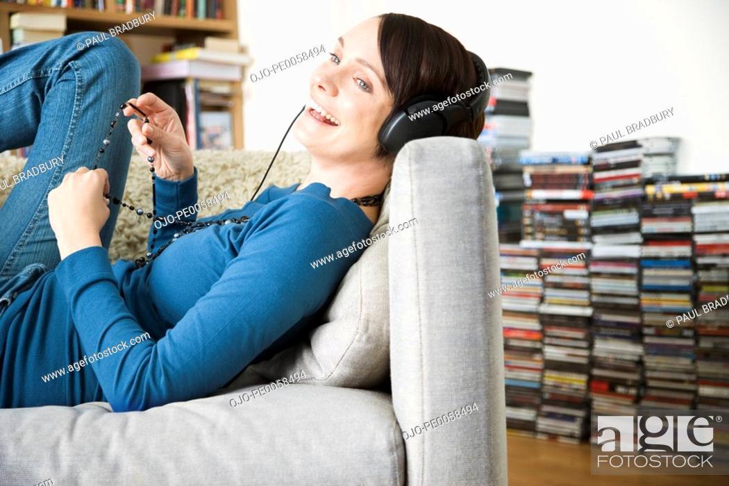 Stock Photo: Woman wearing headphones lying back on sofa.