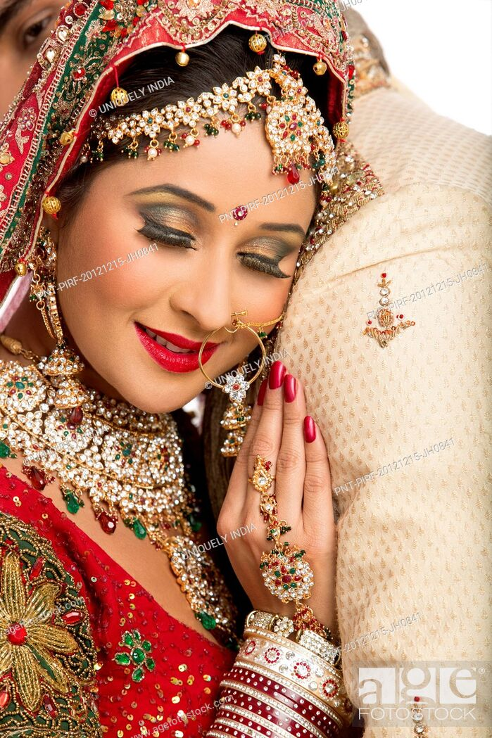 Stock Photo: Close-up of an Indian newlywed couple embracing each other.
