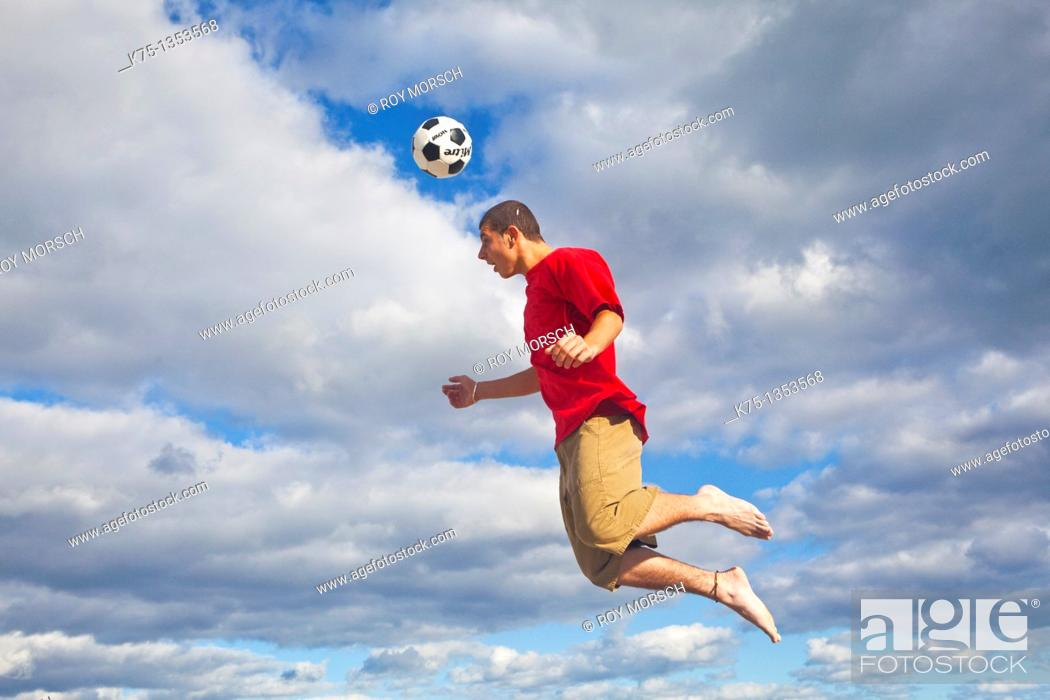 Stock Photo: Hitting soccer ball high in the sky.