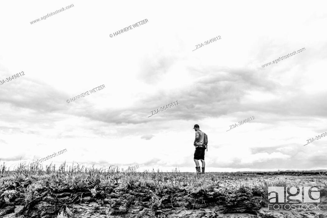 Stock Photo: Man exploring the official nature reserve area and swamp 'The Drowned Land of Saeftinghe' in the southwest Netherlands, located in eastern Zeelandic Flanders.