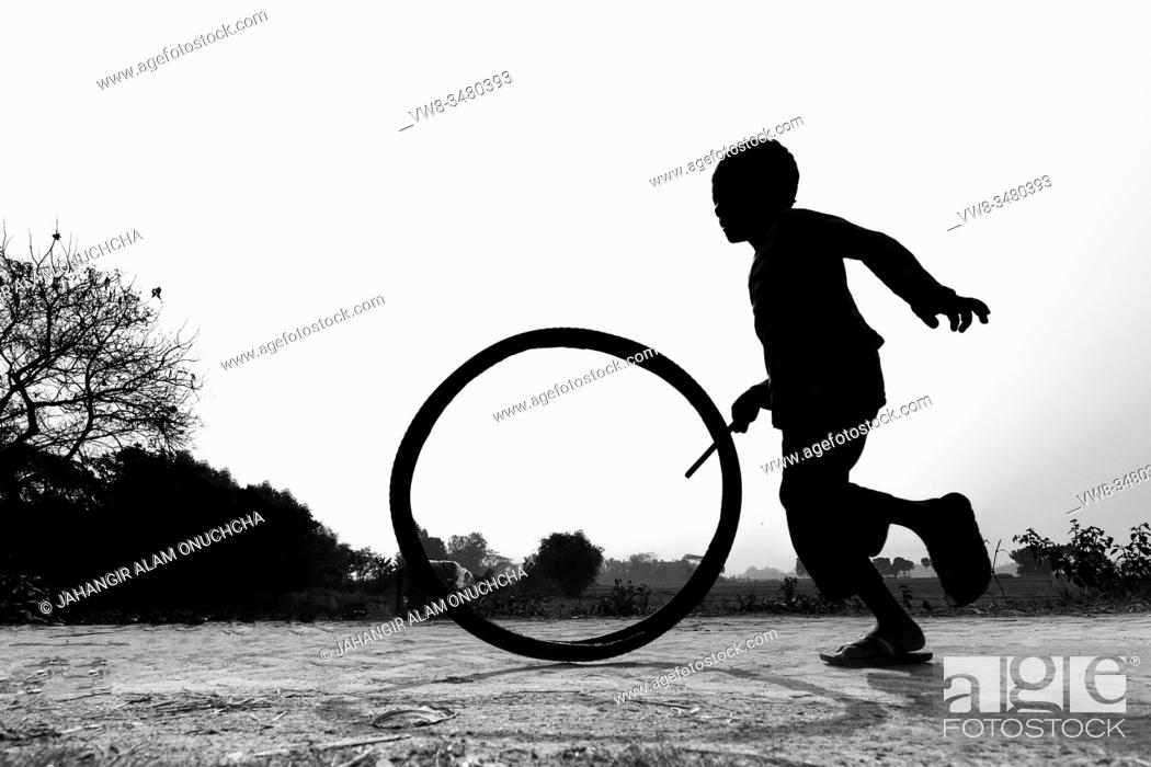 """Stock Photo: Bangladesh â. """" January 24, 2020: A restless boy is playing on the village road with old discarded tires at Savar, Dhaka, Bangladesh."""