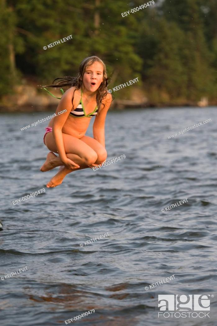 Stock Photo: Young girl jumping into lake, Lake of the Woods, Ontario, Canada.