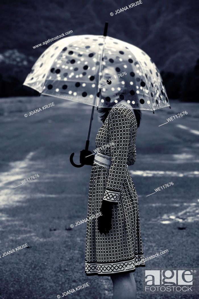 Stock Photo: a woman in a black and white dress with a vintage umbrella.