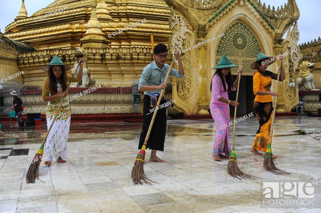 Stock Photo: Yangon, Myanmar, Asia - A group of locals scrubs and cleans the floor of the Maha Wizaya Pagoda with brooms and water.