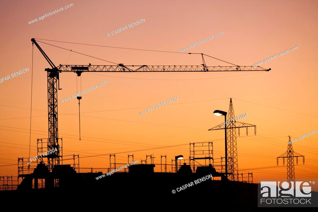 Stock Photo: A construction crane and electricity pylons silhouetted against a sunset sky.