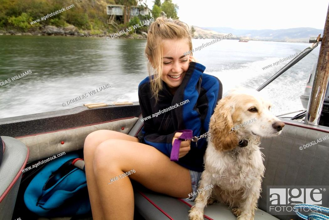 Stock Photo: Girl with her Cocker Spaniel, in a boat on a lake.