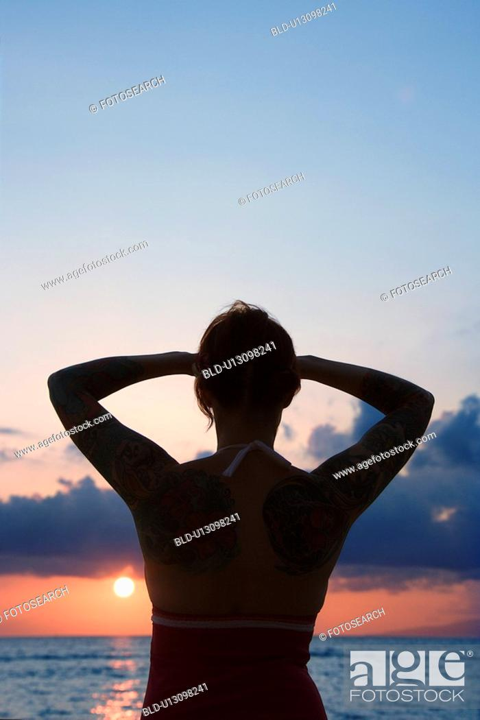 Stock Photo: Attractive tattooed woman on beach at sunset.