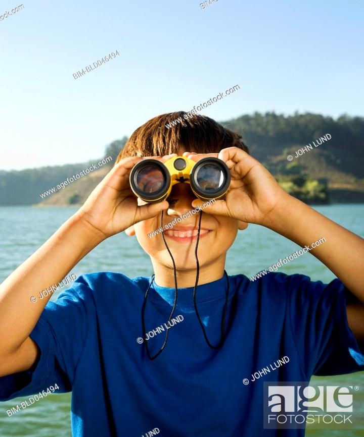 Stock Photo: Hispanic boy looking through binoculars.