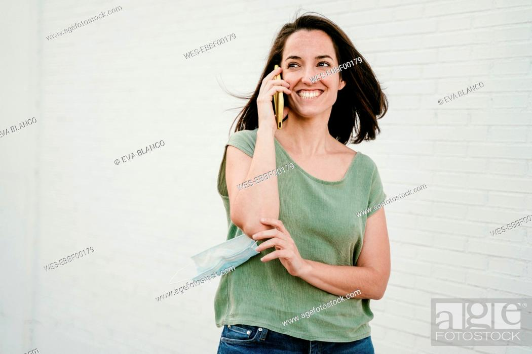 Stock Photo: Portrait of happy woman on the phone with protective mask.